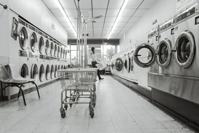 a worker taking out clothes from washing machines kept in the laundry
