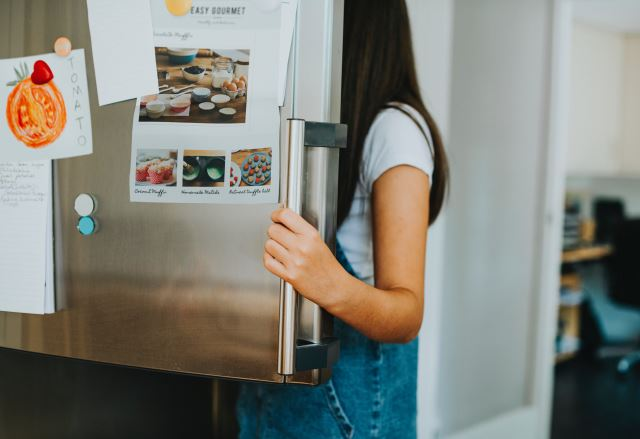 a girl opening the freezer door of a refrigerator